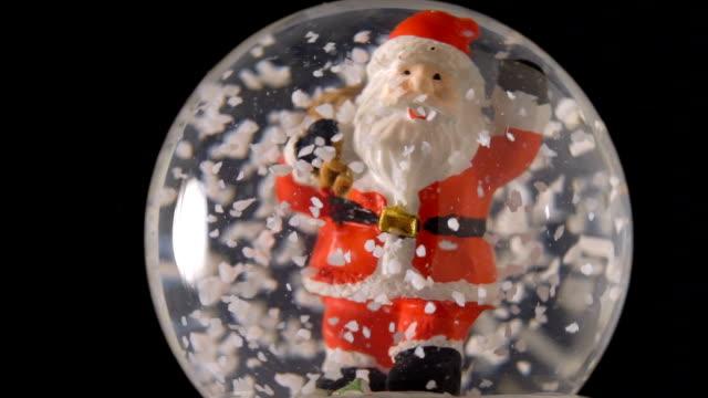 santa claus in snow globe on black background - un singolo oggetto video stock e b–roll