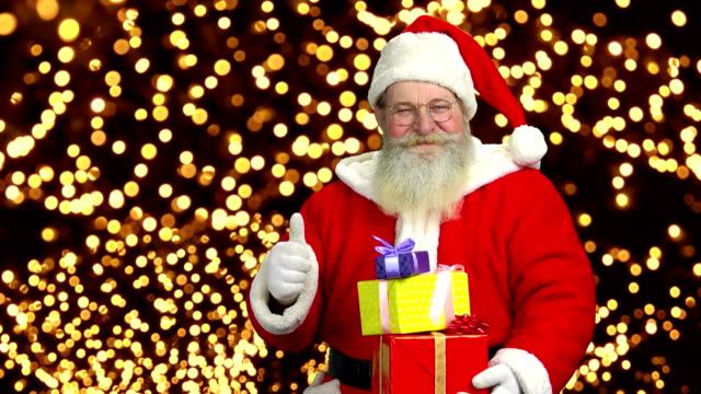 サンタ クロースはプレゼントを開催しています。 - サンタの帽子点の映像素材/bロール