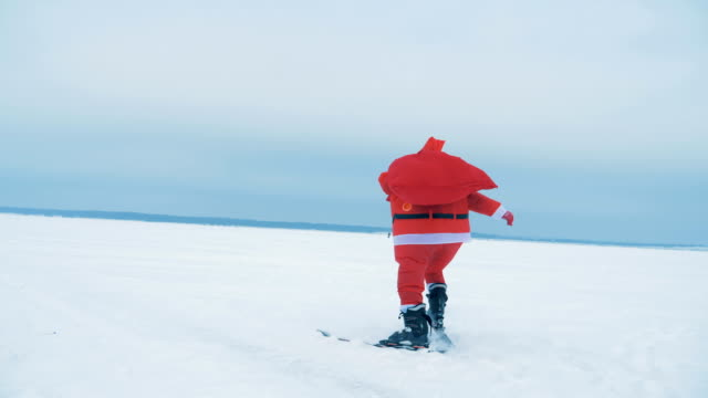 Santa Claus is skiing with a bag of presents across the snow Santa Claus is skiing with a bag of presents across the snow. 4K athleticism stock videos & royalty-free footage