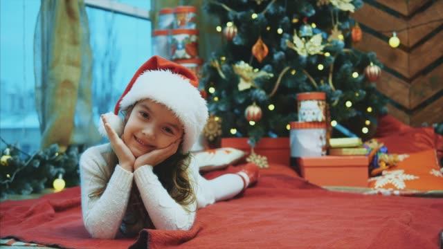 サンタクロースの子供はクリスマスツリーの下に赤い毛布の上に横たわって、頭を左右に動かし、頬に手をつないでいました。 - サンタの帽子点の映像素材/bロール