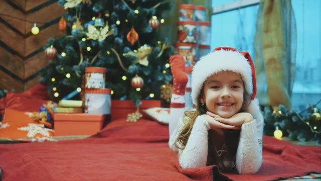 サンタクロースの子供はクリスマスツリーの下に赤い毛布の上に横たわって、赤い靴下で彼女の足を動かし、カメラを幸せで喜んで見ていました。 - サンタの帽子点の映像素材/bロール