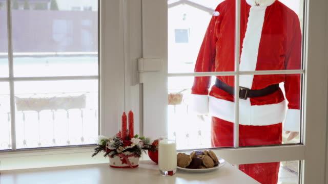 stockvideo's en b-roll-footage met santa claus kijken via een venster op de tabel met melk en koekjes - raam bezoek