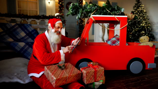 Santa Claus makes list of presents using tablet video