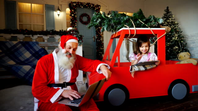 Santa Claus makes thumbs up working with laptop and little girl enjoying with presented tablet video