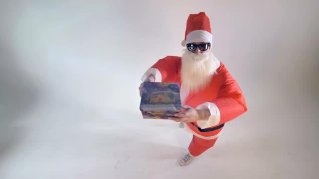 santa claus offers a single gift box raising it up. - santa claus tiptoeing video stock e b–roll