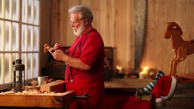 video di natale babbo natale dipinto di giocattoli in corso - incisione oggetto creato dall'uomo video stock e b–roll