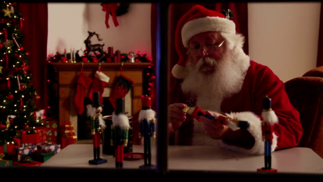 stockvideo's en b-roll-footage met santa claus painting toys in workshop - werkplaats