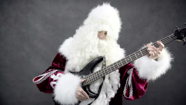 Santa claus plays of the christmas melody jingle bells on the bass guitar video