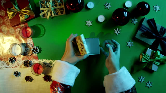Santa Claus plays with fidget spinner and puts it in gift box on New Year table with chroma key, top down shot video