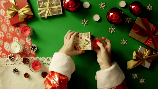 Santa Claus plays with fidget spinner and puts it in gift box on Christmas table with chroma key, top down shot video
