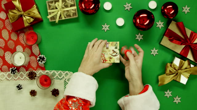 Santa Claus plays with fidget spinner and puts it in gift box on Xmas table with chroma key, top down shot video