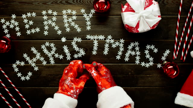 木製のクリスマス テーブル、トップ ショット ダウンでスピナーおもちゃで果たしているサンタ クロース ビデオ