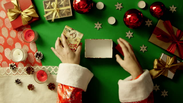 Santa Claus puts credit card in gift box on Christmas decorated table with chroma key, top down shot video