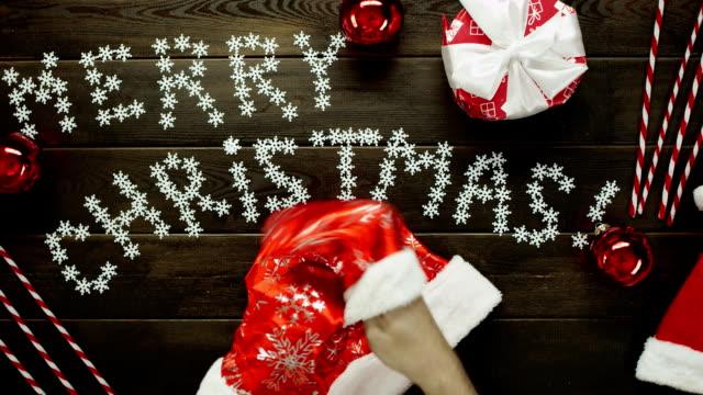 木製装飾クリスマスのテーブル、トップダウンのショットで彼の手袋をつけているサンタ クロース ビデオ