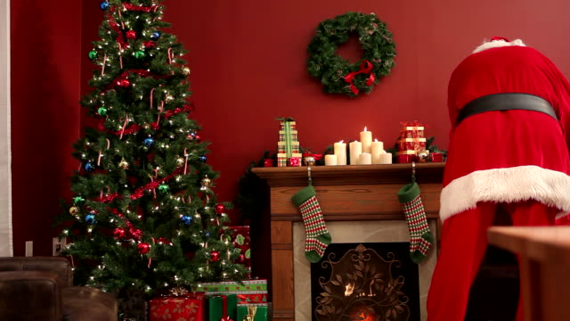 Santa Claus putting gifts in Stockings  christmas stocking stock videos & royalty-free footage