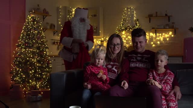 babbo natale mettendo i regali sotto l'albero di natale in camera con la famiglia - christmas movie video stock e b–roll