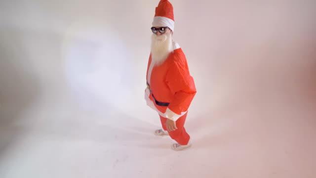 santa claus reaches high up to offer a gift box. - santa claus tiptoeing video stock e b–roll