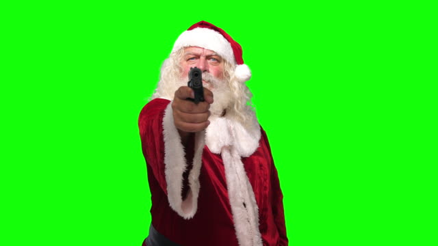 Video Santa Claus robber with a gun threating camera in front of chroma key green screen background