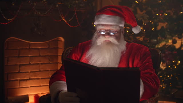 Santa Claus sitting at his home in a comfortable chair and reading a letter
