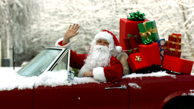 vidéos et rushes de père noël assis en cabriolet le tout avec des cadeaux de noël - homme faire coucou voiture