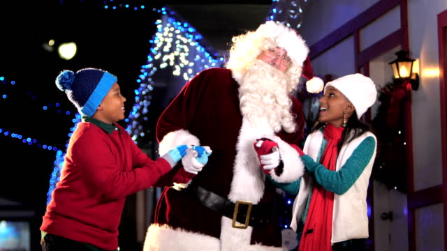 Santa Claus talking with two African-American children