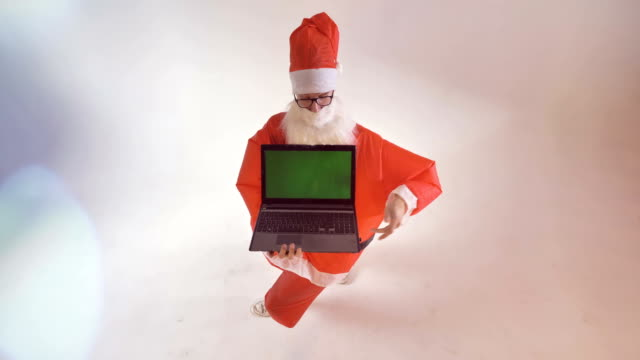 Santa Claus turns around and shows a brand new laptop screen with green background.