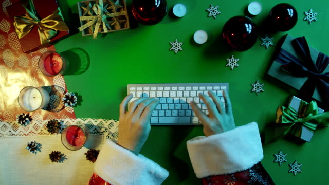 Santa Claus typing on wireless keyboard by New Year table with chroma key, top down view video