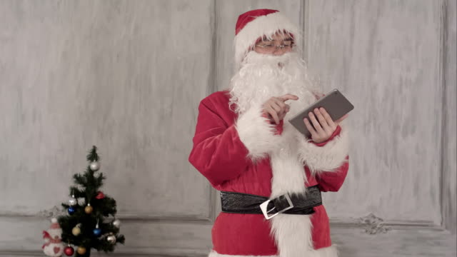 santa claus using tablet computer on white background - holiday and invoice family video stock e b–roll