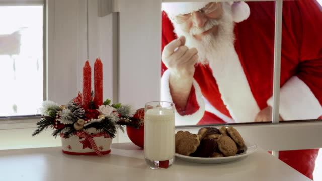 stockvideo's en b-roll-footage met santa claus wilt proeven van de melk en koekjes en kijk door een glas - raam bezoek