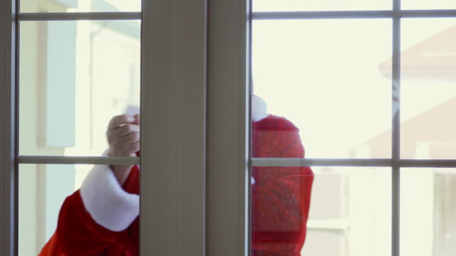 Santa Claus with bag of presents knocking in window