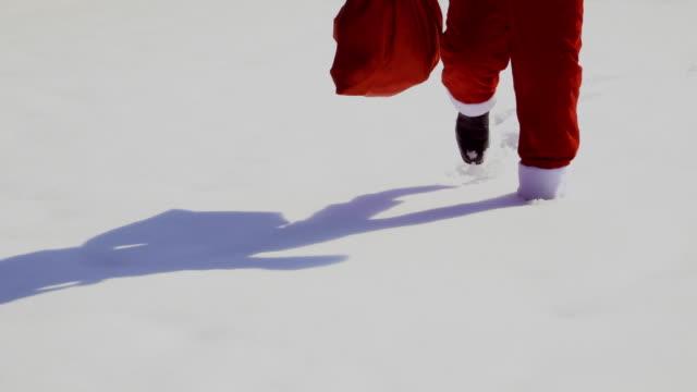 weihnachtsmann mit geschenken zu fuß, auf dem schnee - nikolaus stiefel stock-videos und b-roll-filmmaterial
