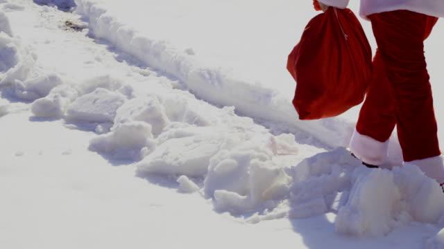 santa claus mit tasche gehen auf schnee weg - nikolaus stiefel stock-videos und b-roll-filmmaterial
