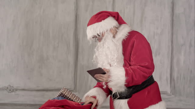 Santa claus with tablet pc computer checking gift bag video