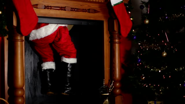 Santa / Father Christmas coming down the chimney Stock HD video clip footage of Father Christmas / Santa claus coming down the chimney on Christmas eve with his sack full of toys - Two different shots, with a camera dolly motion.  christmas stocking stock videos & royalty-free footage