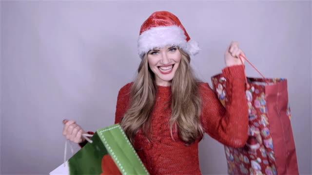 santa girl holding shopping bags, enjoying snowfall in studio. - djurarm bildbanksvideor och videomaterial från bakom kulisserna