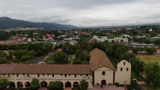 vídeos de stock e filmes b-roll de santa ines mission in solvang california town aerial - uva shiraz
