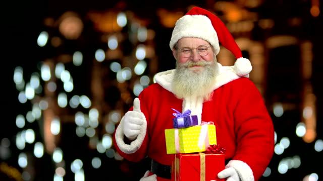 サンタは、ギフト ボックスを保持しています。 - サンタの帽子点の映像素材/bロール