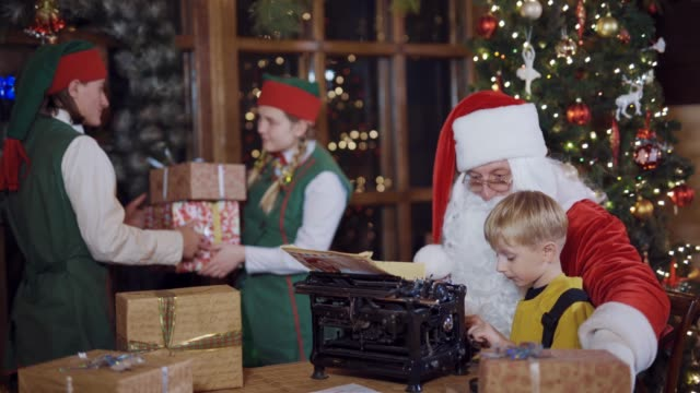 Bидео Santa is teaching little boy to print on an old typing machine.