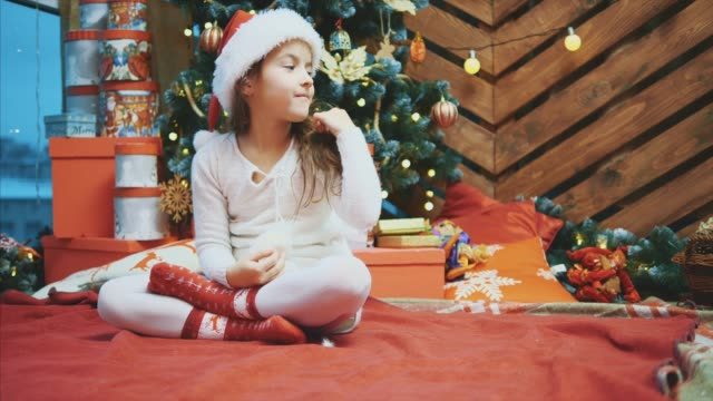 Santa kid sitting near christmas tree, pointing at copyspace for text or product on her side.