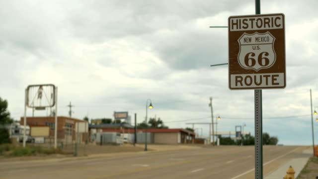 stockvideo's en b-roll-footage met 4k santa rosa (new mexico) historische route 66 weg teken auto's rijden door de wolken - arizona highway signs