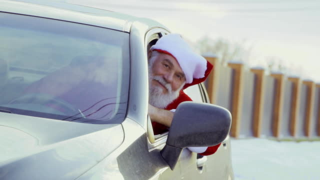vidéos et rushes de santa shake touches à l'affût de nouvelle voiture, slow motion - homme faire coucou voiture
