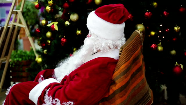 Santa sitting in comfortable rocker chair by Christmas tree, magic Santa sitting in comfortable rocker chair by Christmas tree, magic atmosphere rocking chair stock videos & royalty-free footage