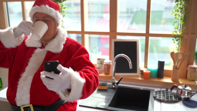 Santa taking a break from work and surfing the net using smartphone at home