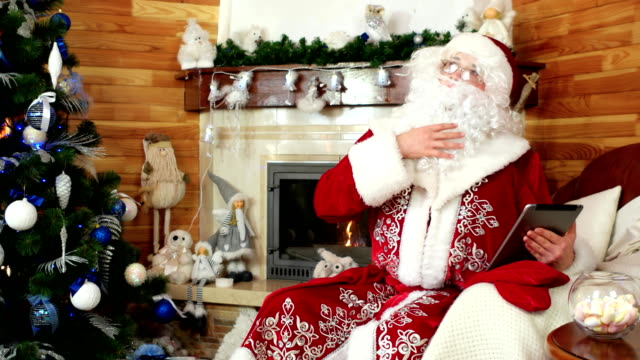santa using tablet, santa claus choosing presents with the help of gadget, new ideas, fireplace - holiday and invoice family video stock e b–roll