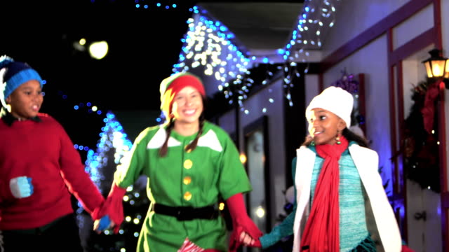 Santa's elf skipping through village with two children