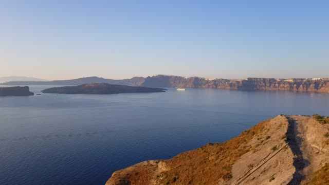 santorini caldera. view of the volcanic complex of santorini thera, including skaros rock, imerovigli and oia towards the sun - fire filmów i materiałów b-roll