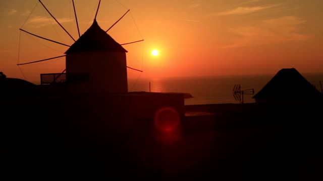 Santorini with famous windmill in Greece, Oia village on beautiful sunset video