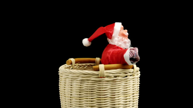 Santta Claus toy in red suit in wicker basket on black background. video