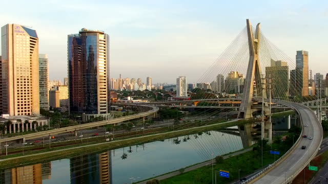 Sao Paulo Video flying over Marginal Pinheiros, an important highway of Sao Paulo. The famous cable-stayed bridge is on background. The sunlight reflecting on a modern building. marginal pinheiros stock videos & royalty-free footage