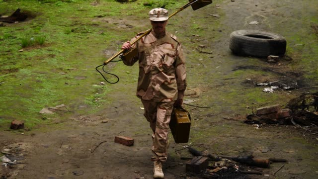 sapper with mine detector walks in ruined place - libia video stock e b–roll